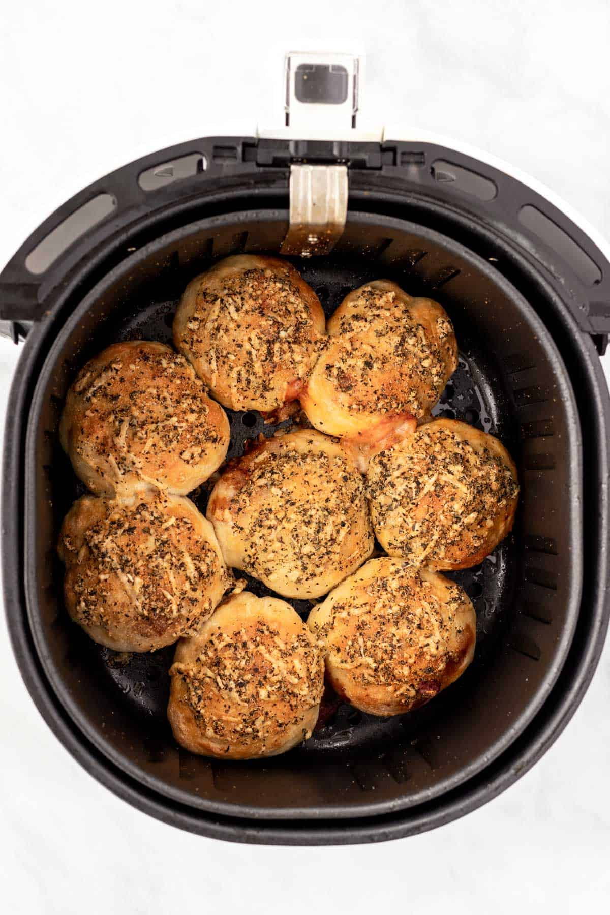 Cooked golden brown pizza rolls in the air fryer basket.