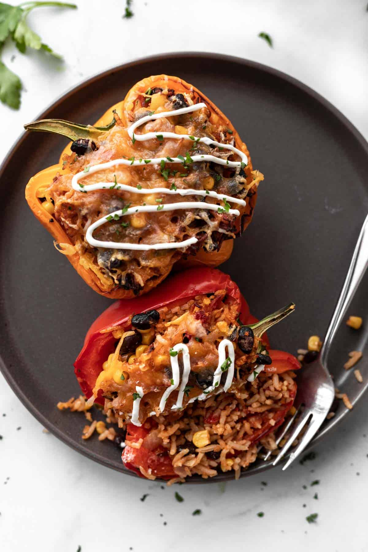 2 air fryer stuffed peppers drizzled with sour cream on a gray plate with a fork and filling pouring out.