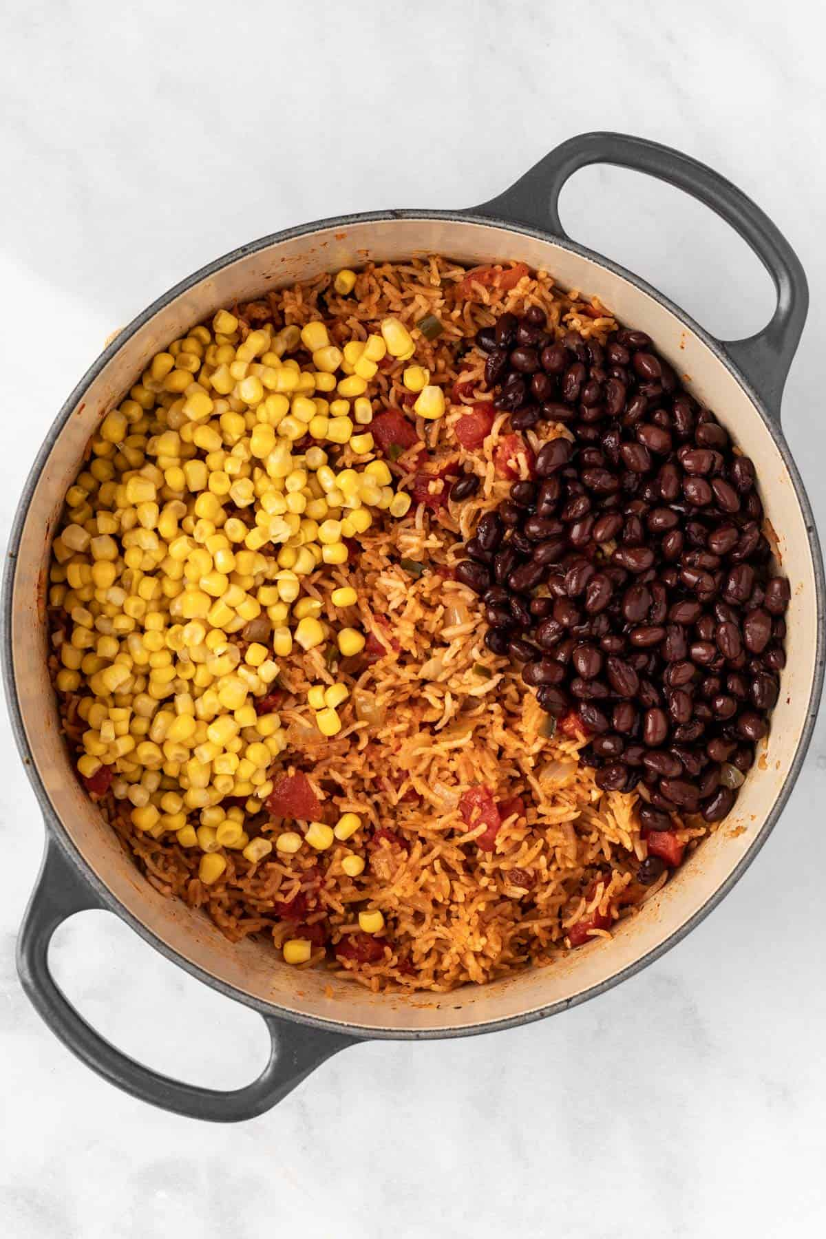 Cooked rice mixture in a dutch oven with corn and black beans on top.