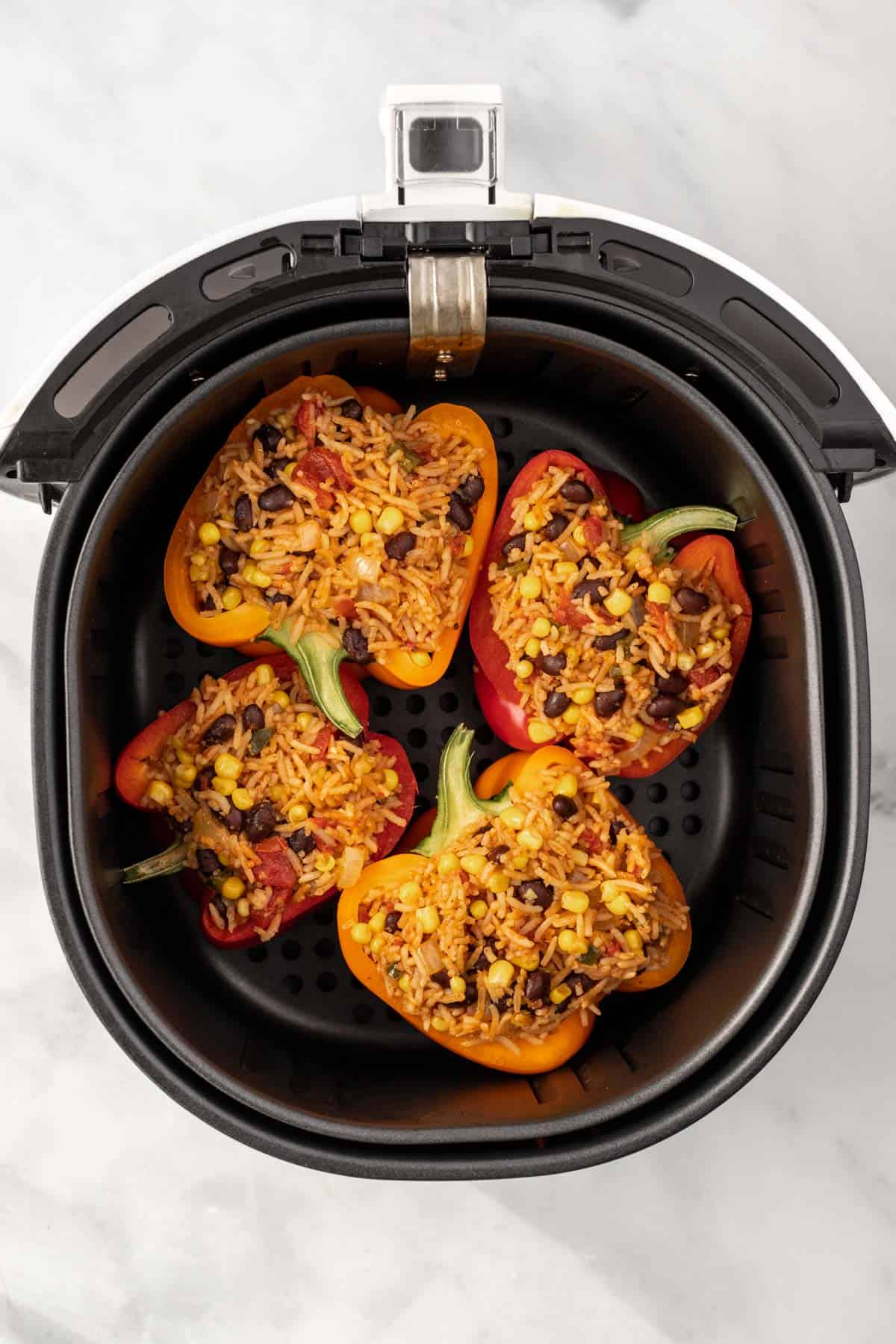 Uncooked stuffed peppers in an air fryer basket.