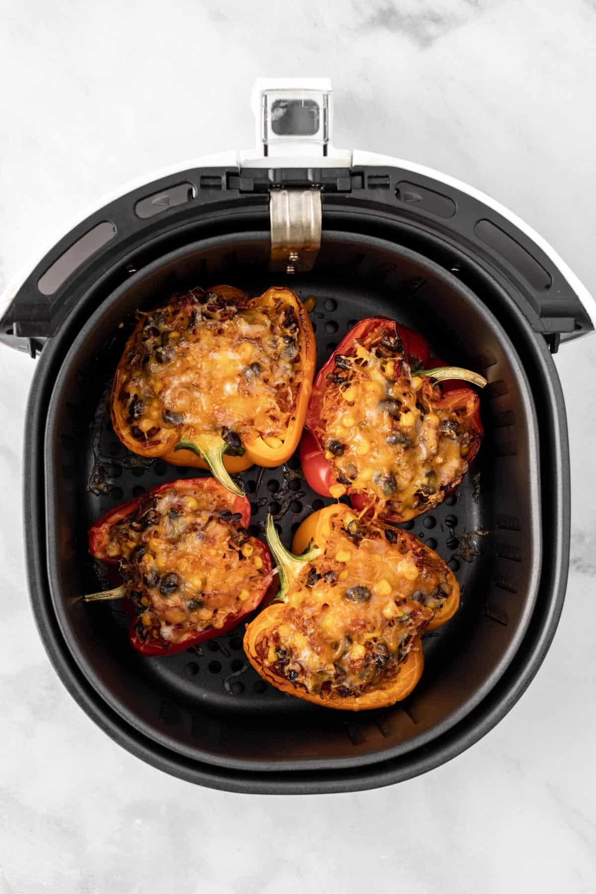 Cooked stuffed peppers with melted cheese on top in an air fryer basket.