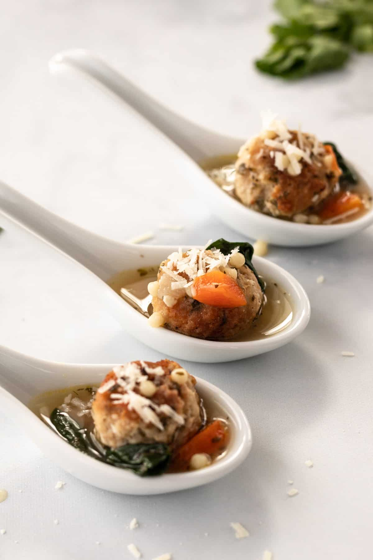 3 porcelain spoons filled with broth, meatballs, spinach, and parmesan cheese all lined up next to each other.