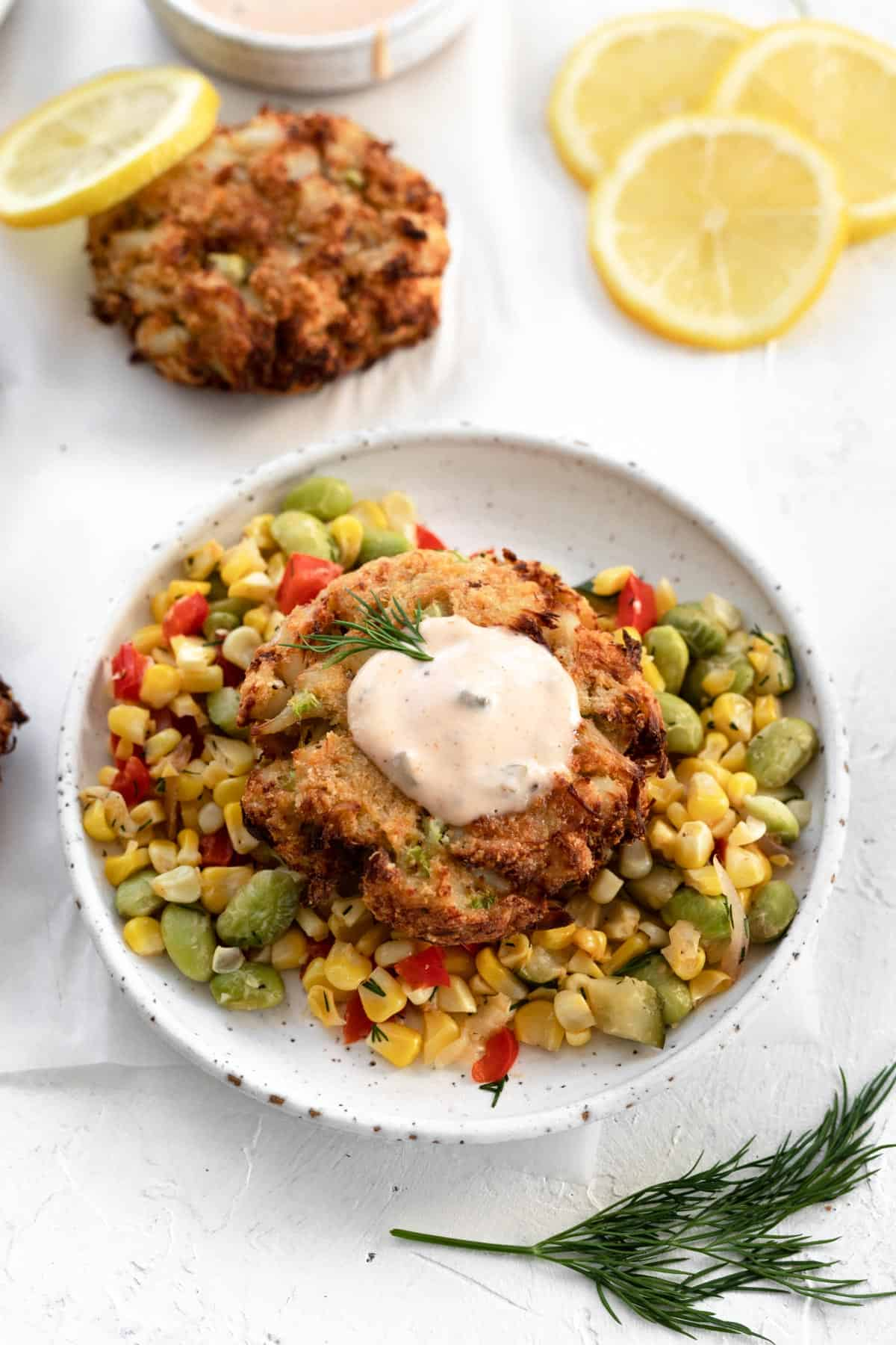 A crab cake on top of corn succotash on a white plate with a dollop of homemade remoulade sauce on top.