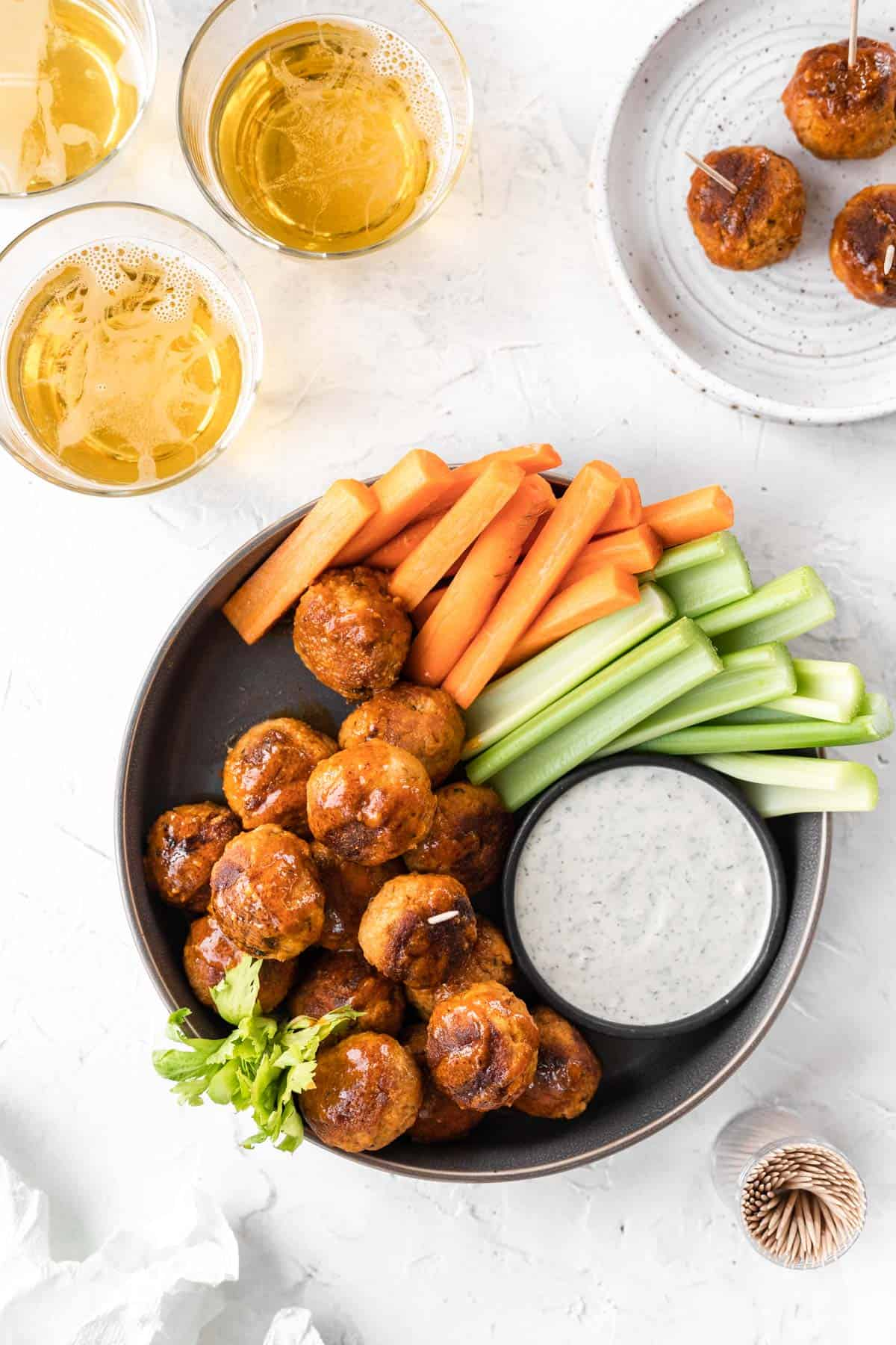 A serving platter full of meatballs with ranch and vegetables off to the side and 3 meatballs on a small appetizer plate.