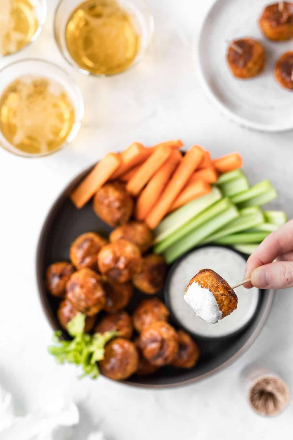 A hand dipping a buffalo turkey meatball in feta ranch with glasses of beer, celery and carrot sticks, and a jar of toothpicks off to the side.