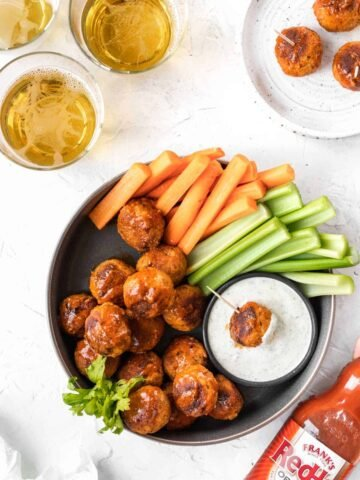 Buffalo turkey meatballs in a serving dish with a side of ranch, celery, and carrot sticks.