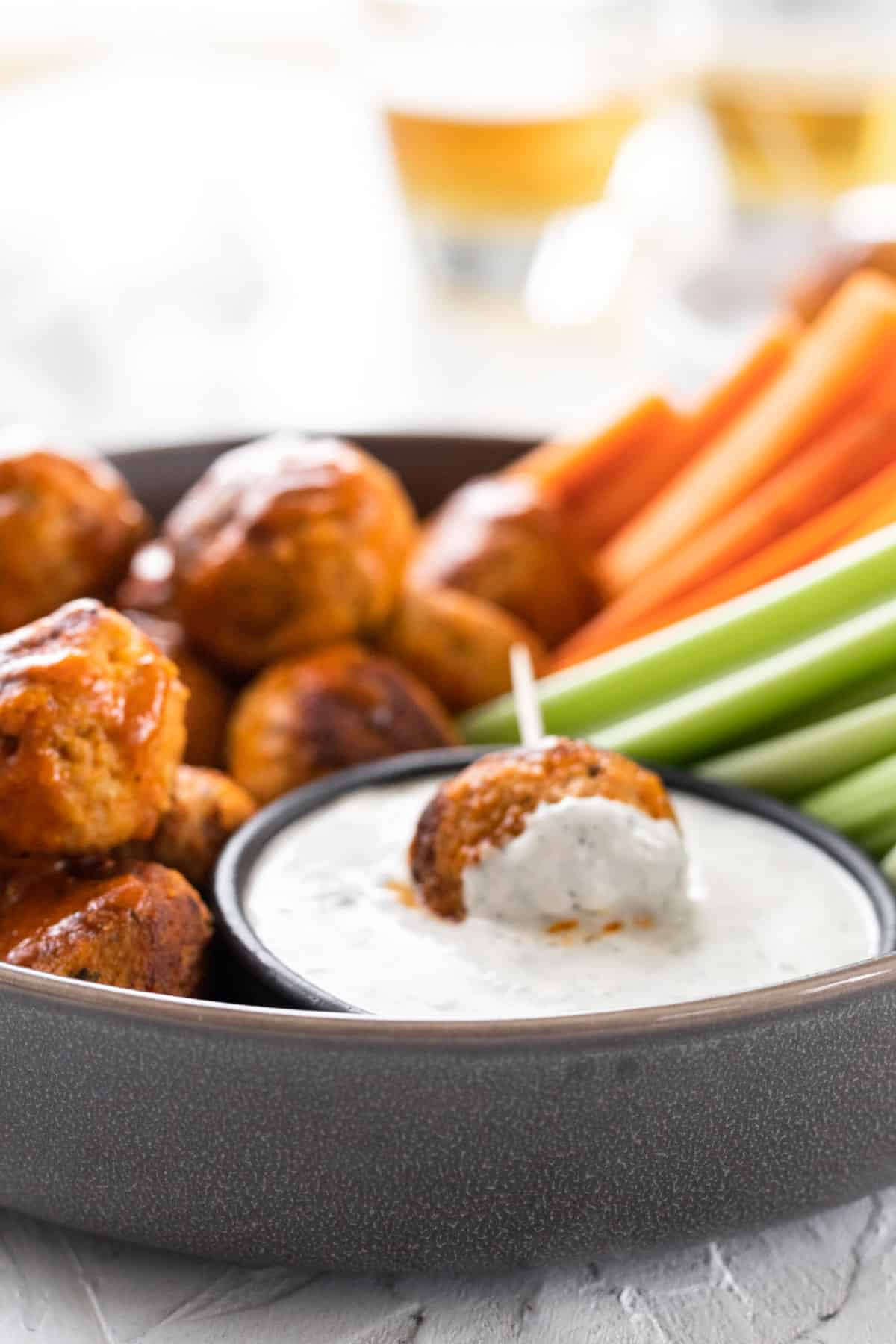 A buffalo turkey meatball on a toothpick dipped in feta ranch.
