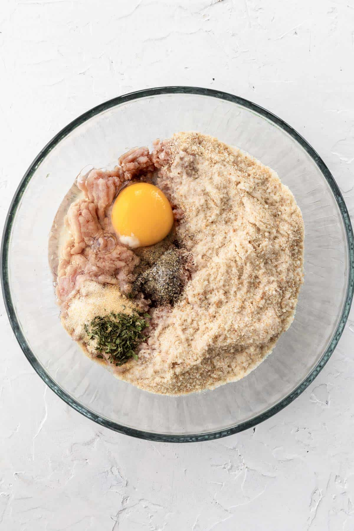 Turkey meatball ingredients in a glass bowl.
