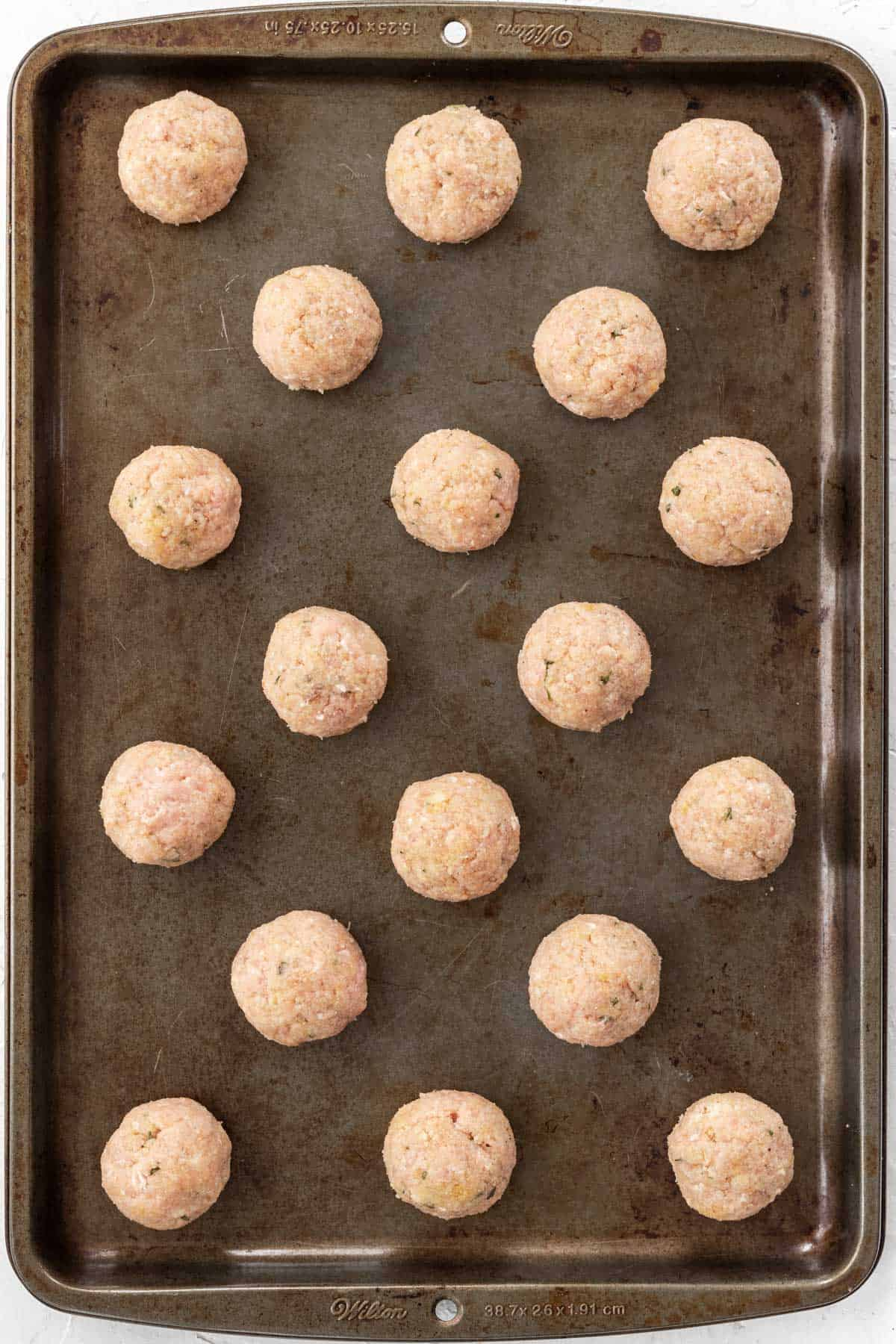 Raw meatballs on a baking sheet.