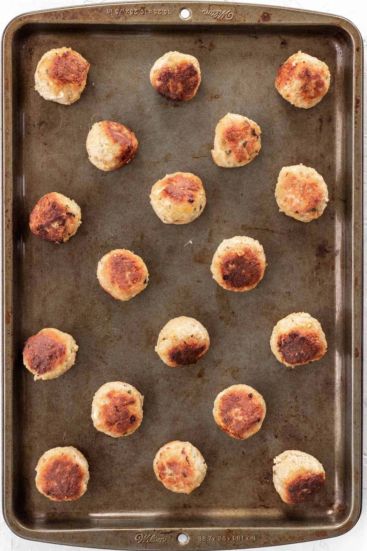 Browned meatballs on a baking sheet.
