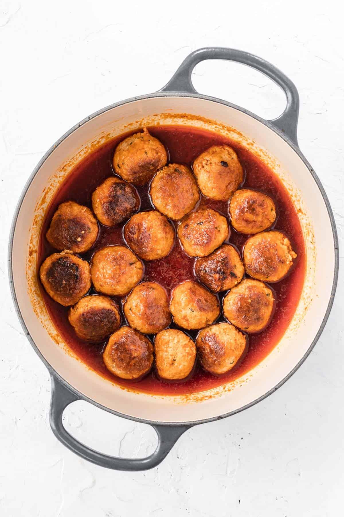 Turkey meatballs in buffalo sauce inside a dutch oven.