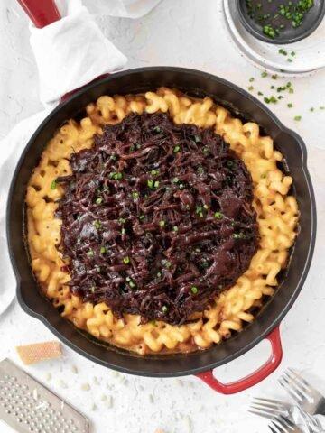 Creamy cheddar baked brisket mac and cheese in a large cast iron skillet with chopped chives and grated cheese around it.