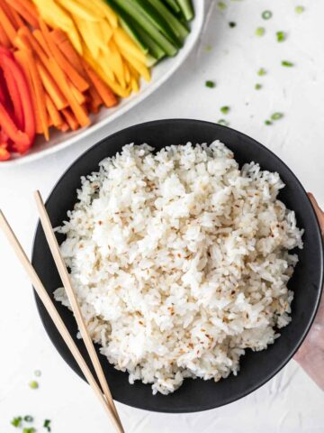 A bowl of perfect instant pot sushi rice held in the air with chopsticks resting on top. Below is a plate of sliced vegetables.
