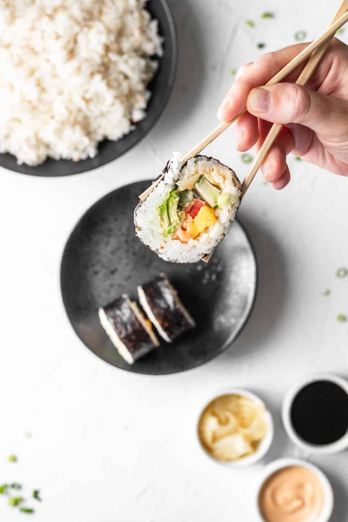 A hand holding chopsticks in the air with a piece of sushi at the end. Below is a bowl of rice, more pieces of sushi, pickled ginger, soy sauce, and spicy mayo.
