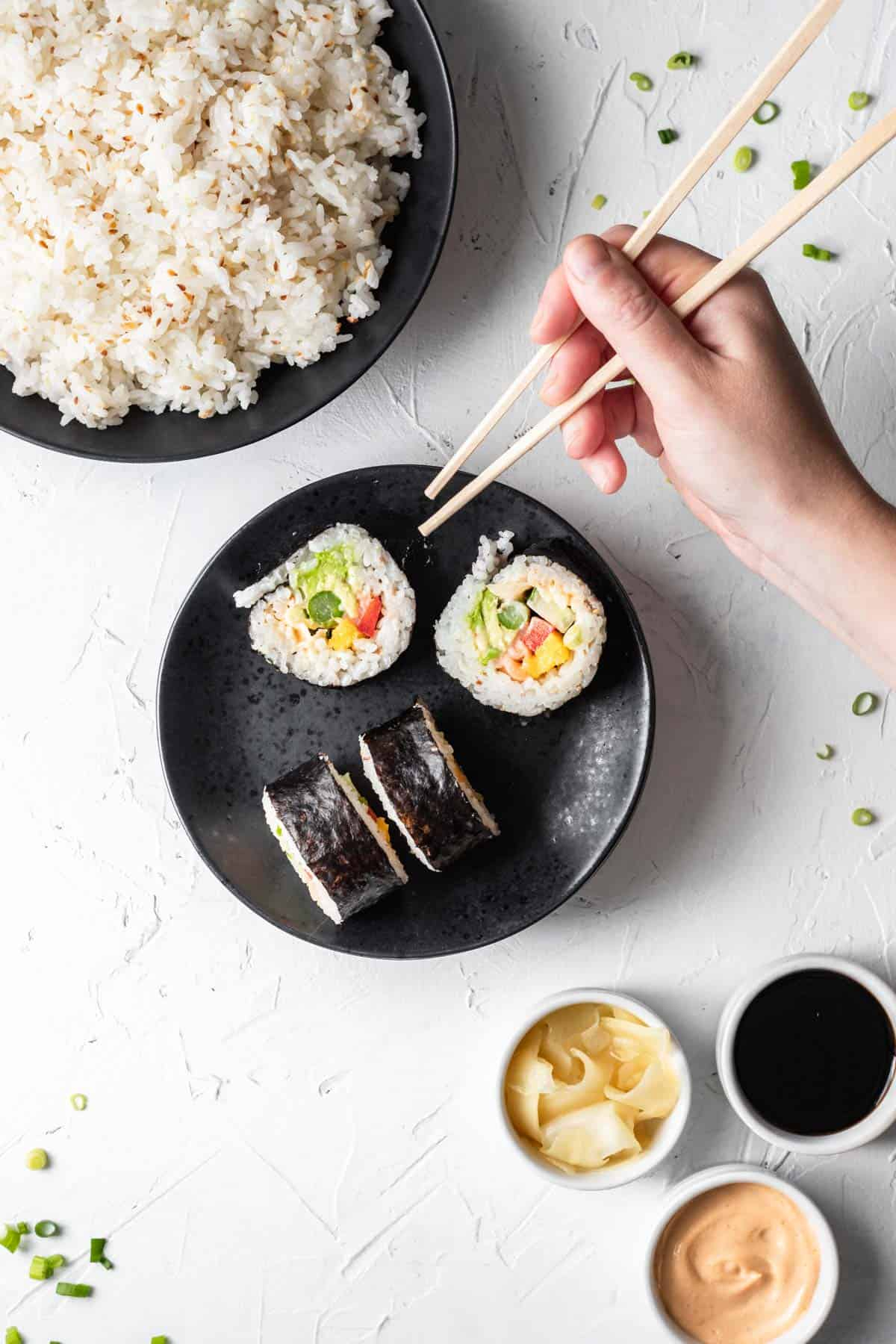 4 pieces of rolled sushi on a black plate with cooked sushi rice above and a hand with chopsticks to the right.