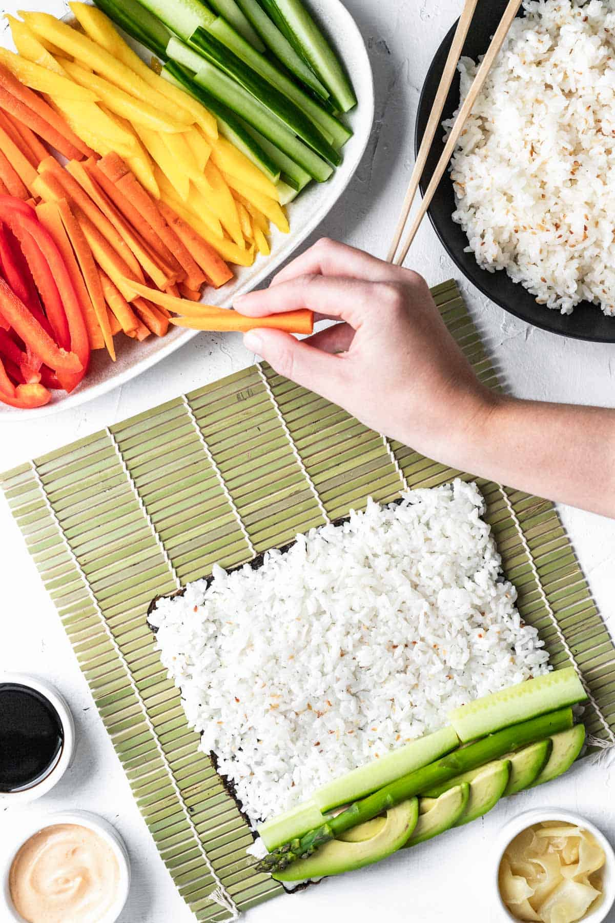 A hand grabbing sliced vegetables to place on top of sushi rice covered nori.
