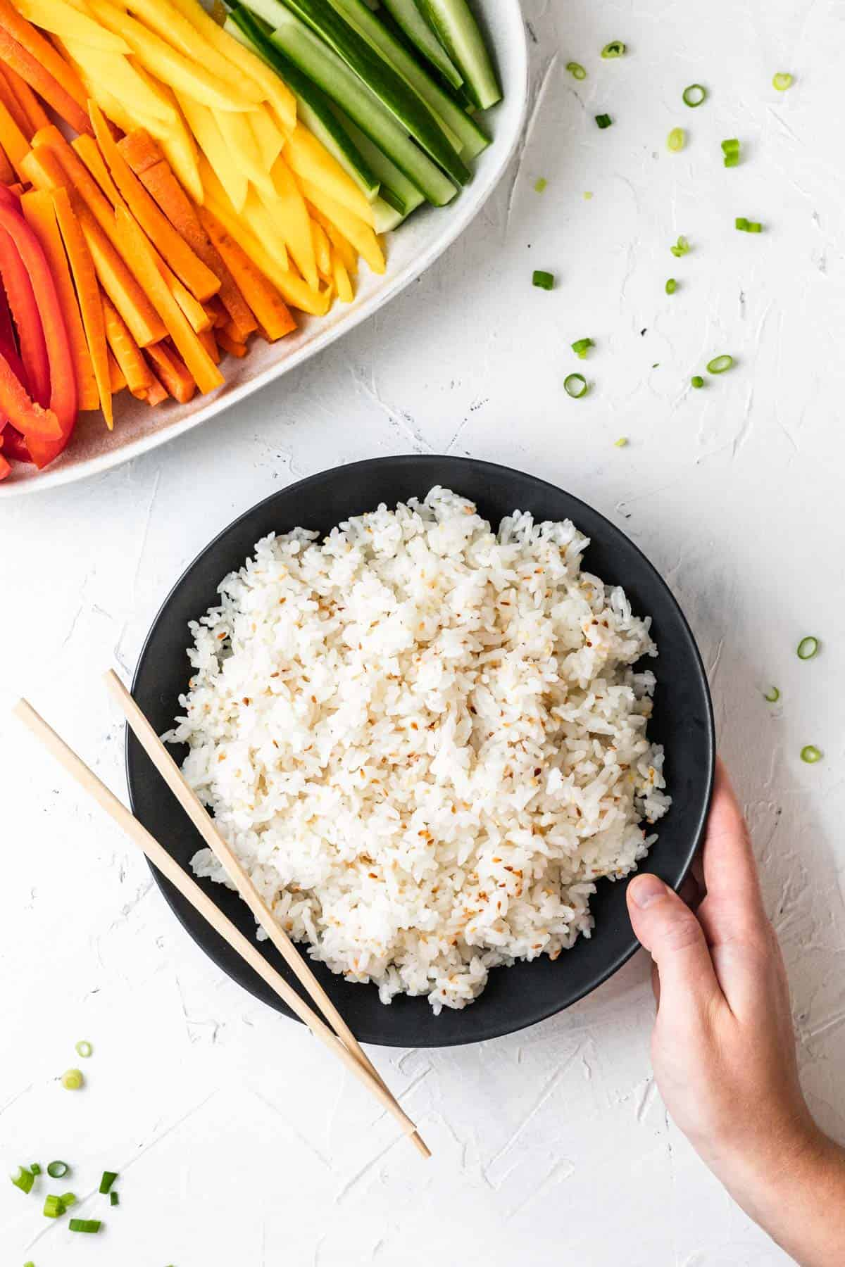 A hand placing a black bowl filled with sushi rice on a white table next to a plate of sliced vegetables.