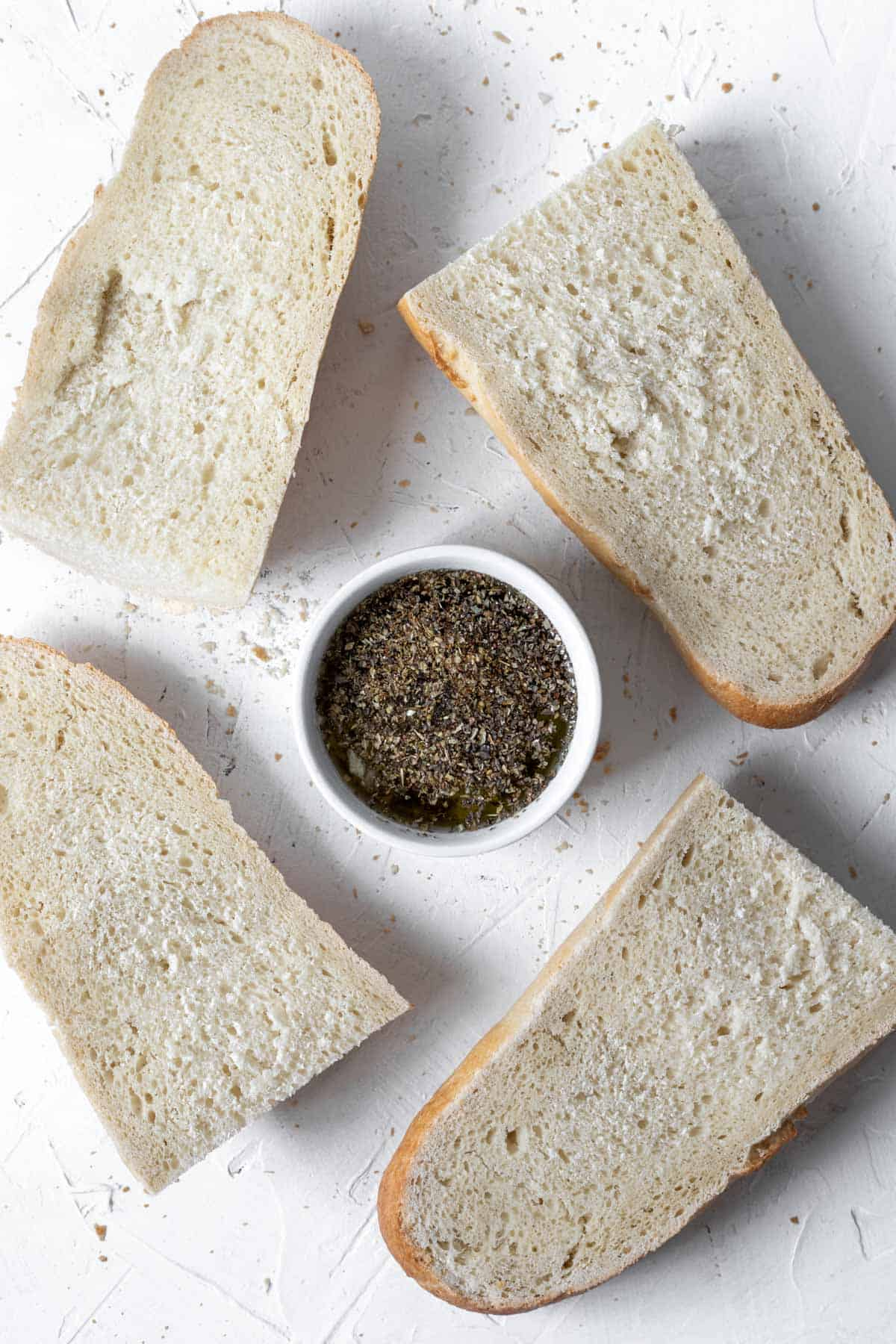 French bread cut into quarters with a garlic herb olive oil mixture in a small bowl.