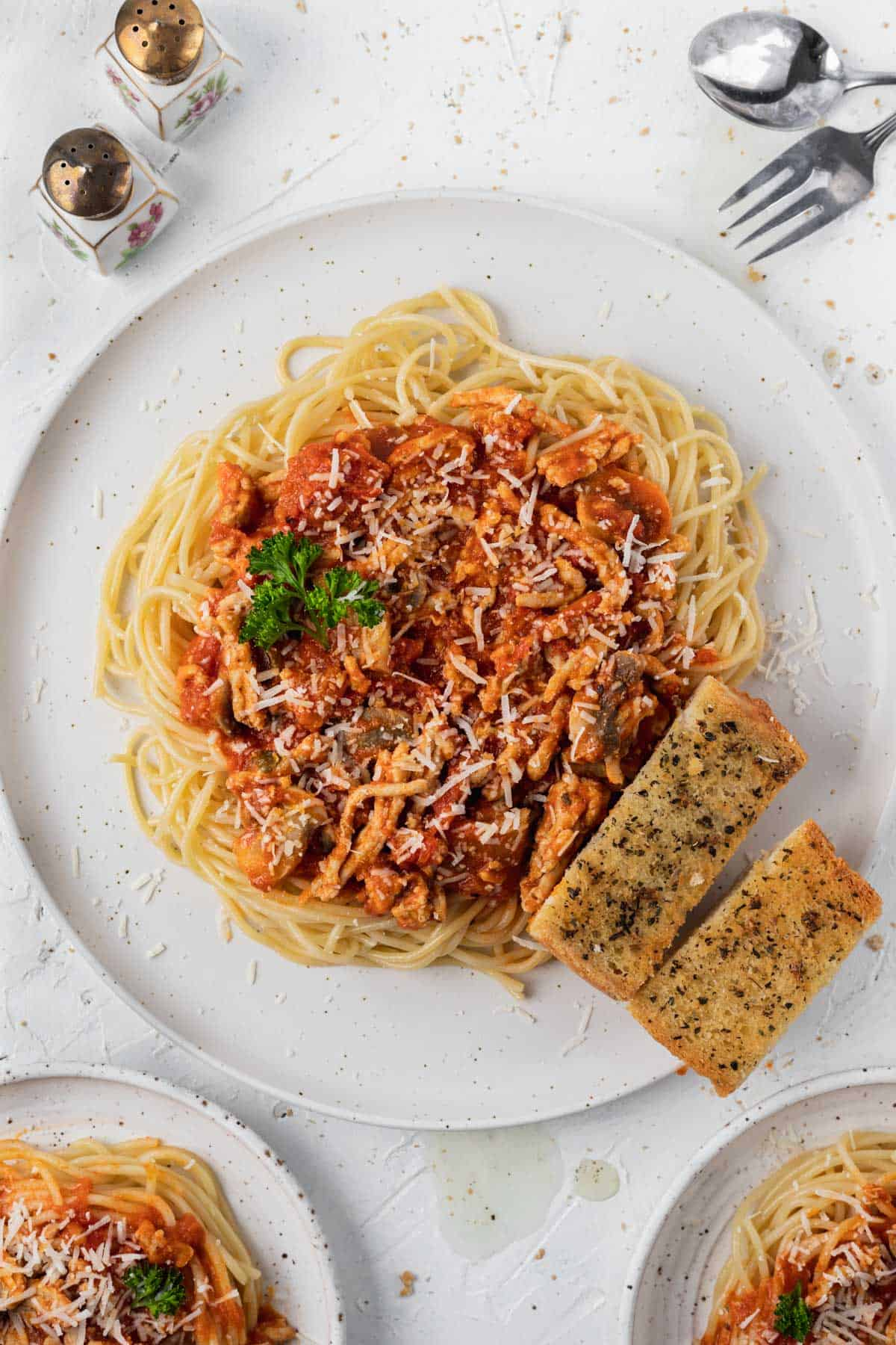 Quick and easy air fryer garlic bread served with a plate of spaghetti.