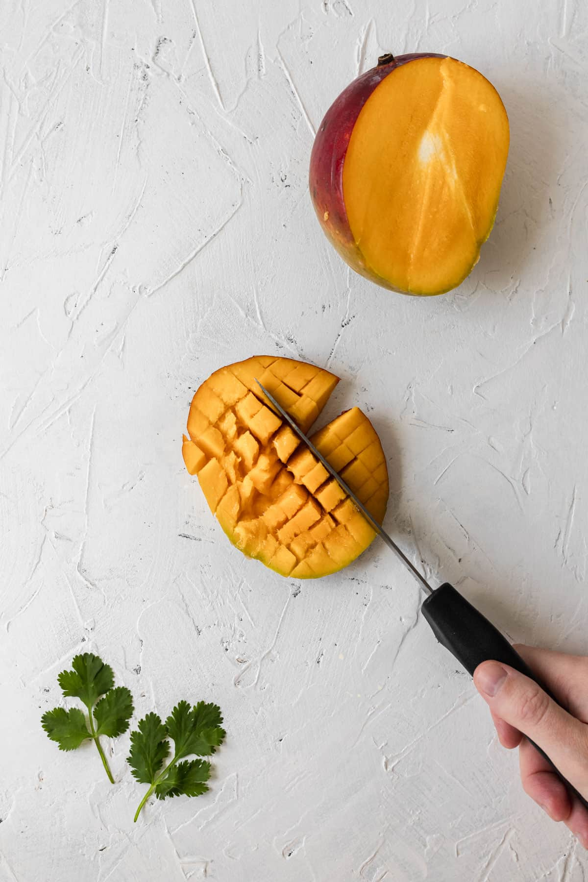 A knife cubing the inside of part of a mango.