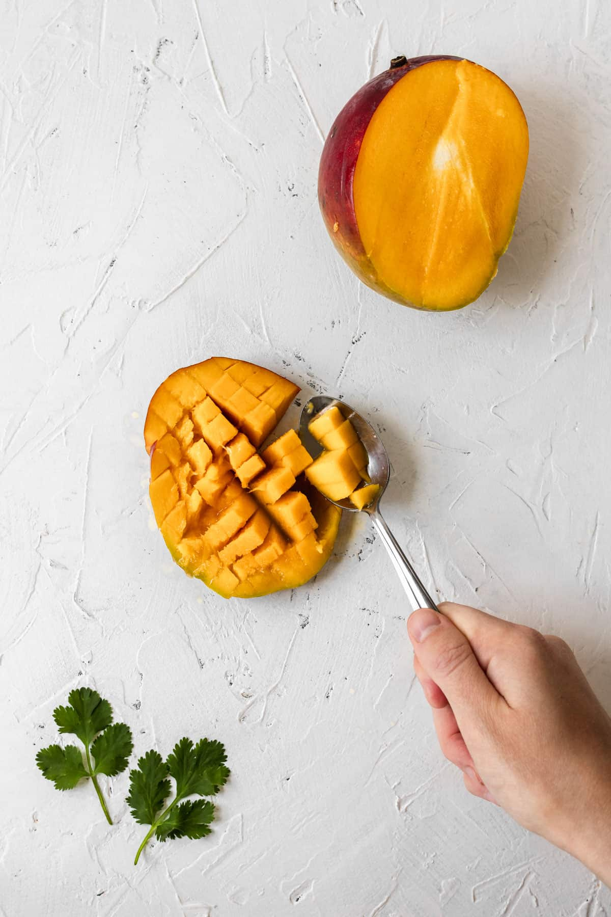 A spoon peeling the skin back and scooping out the cubed inside of mango.