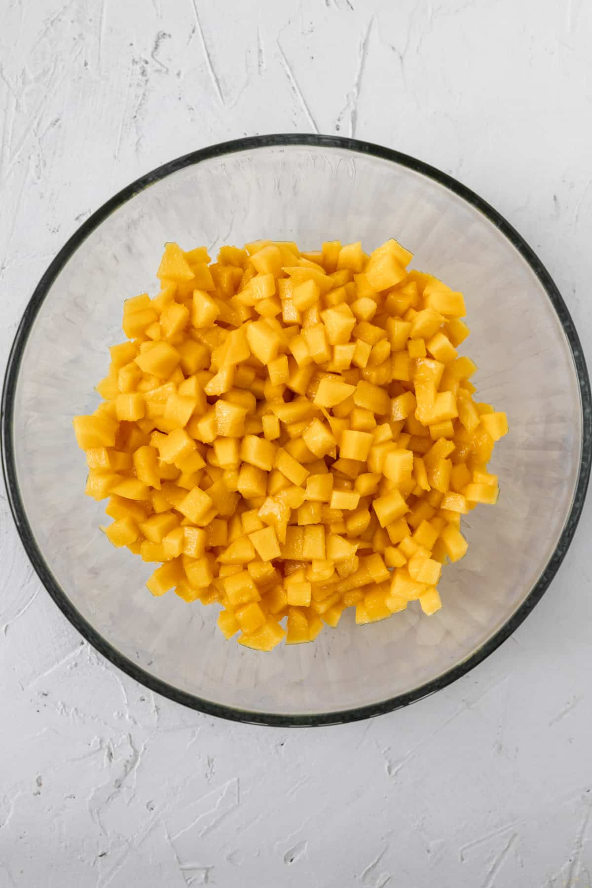 Cubed mango in a glass bowl.
