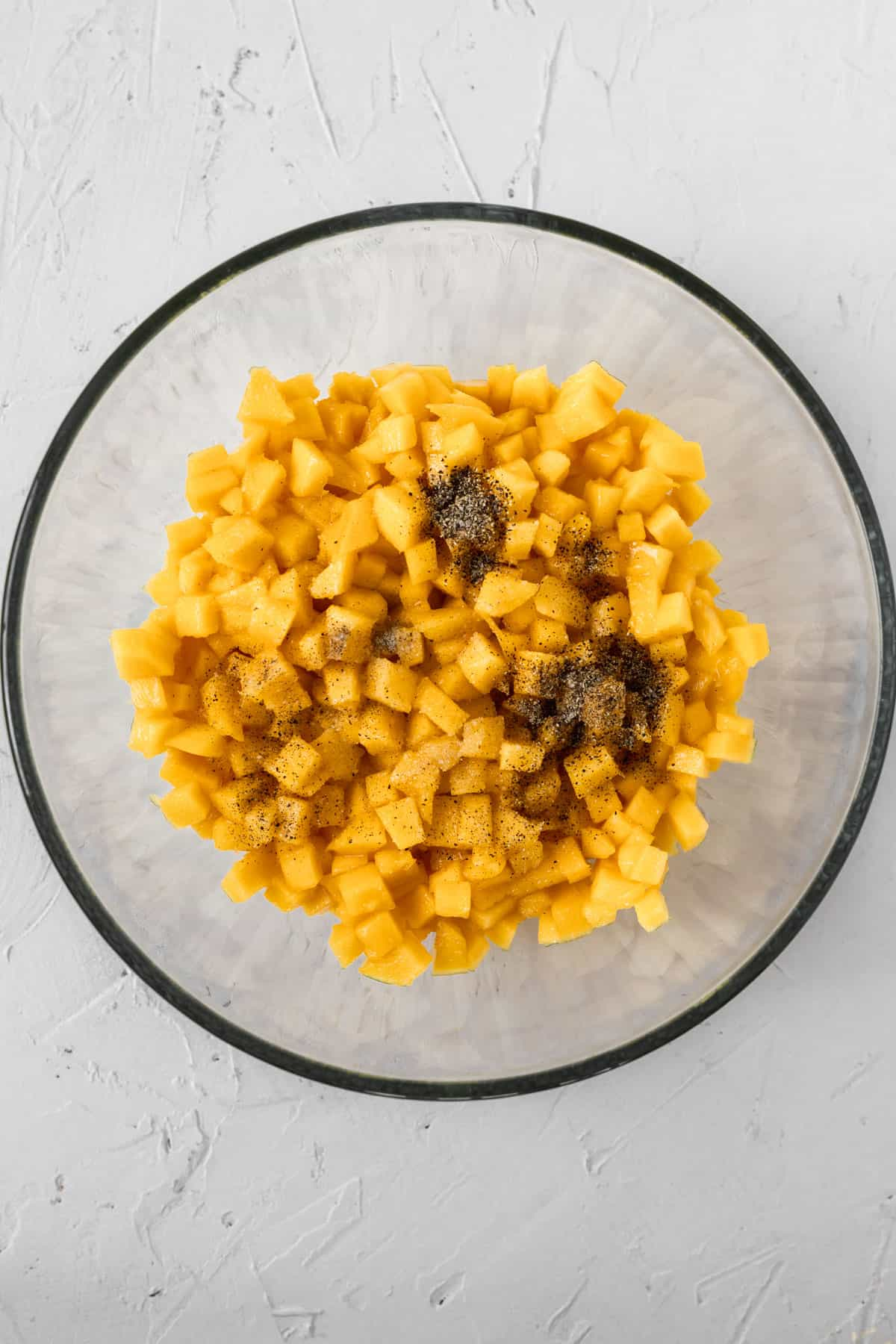 Cubed mango and seasonings in a glass bowl.