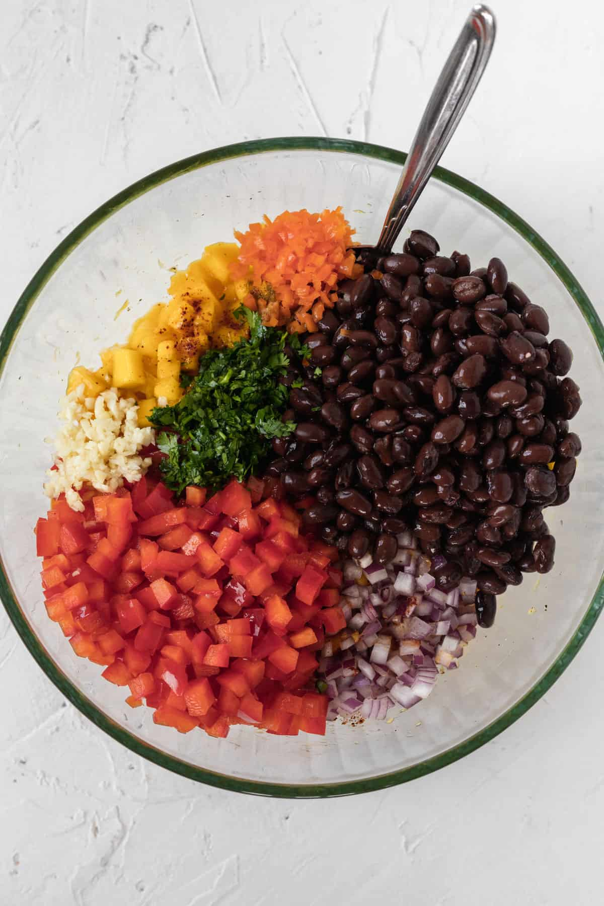 All the ingredients for spicy mango salsa chopped up and piled in a glass bowl.