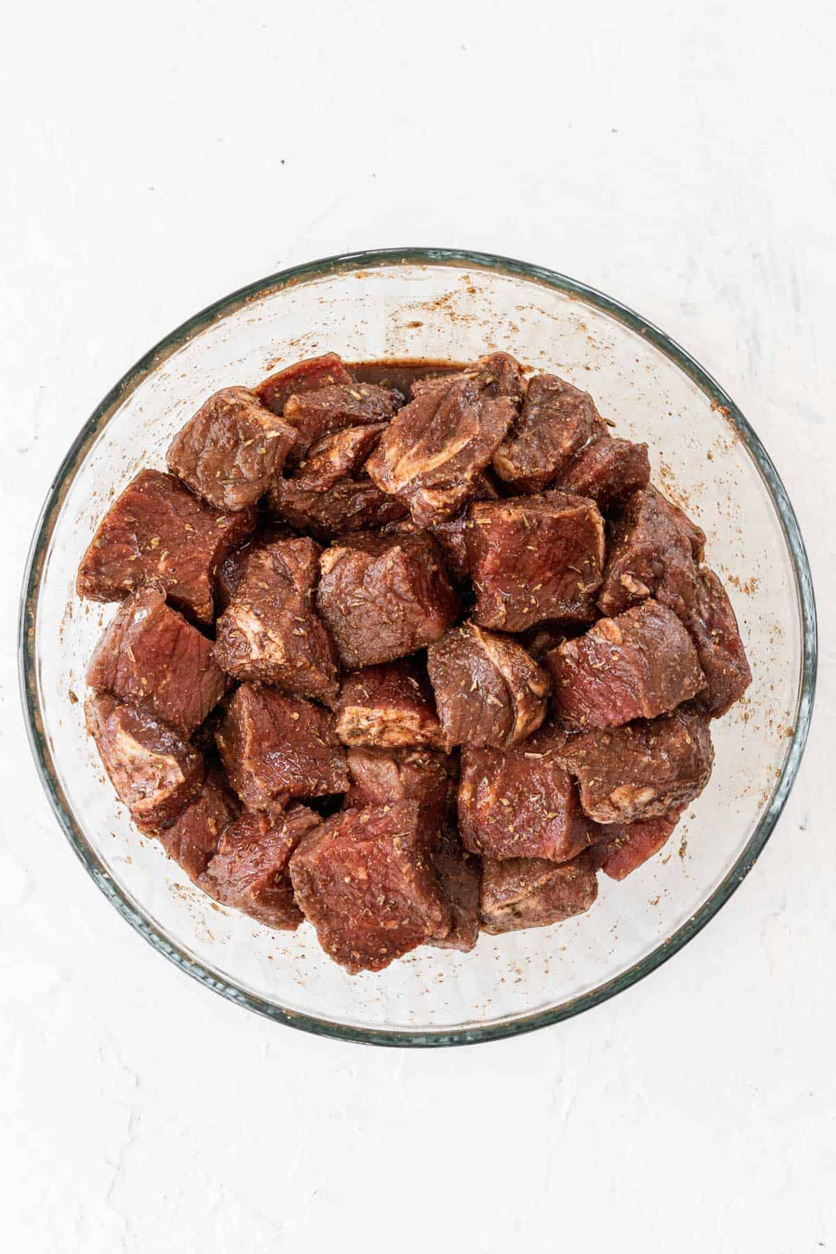 Cubed steak in a glass bowl topped with a balsamic marinade.