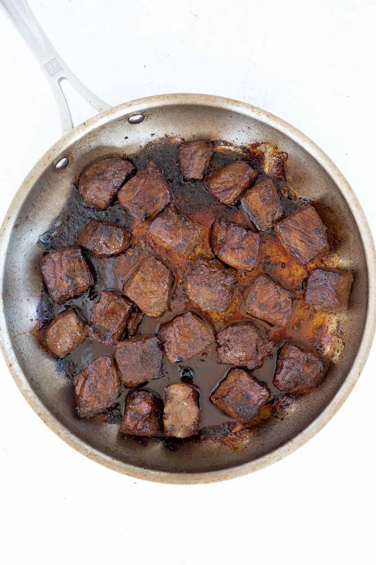 Steak bites cooked crispy in a skillet.