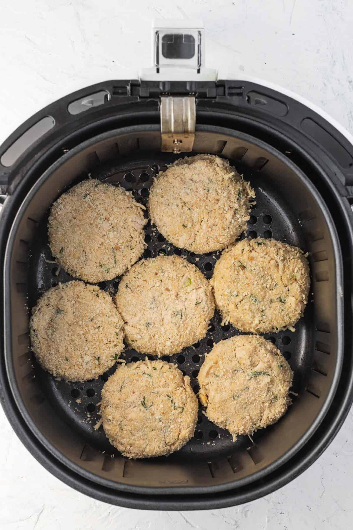 Formed uncooked chicken patties in a basket of an air fryer.