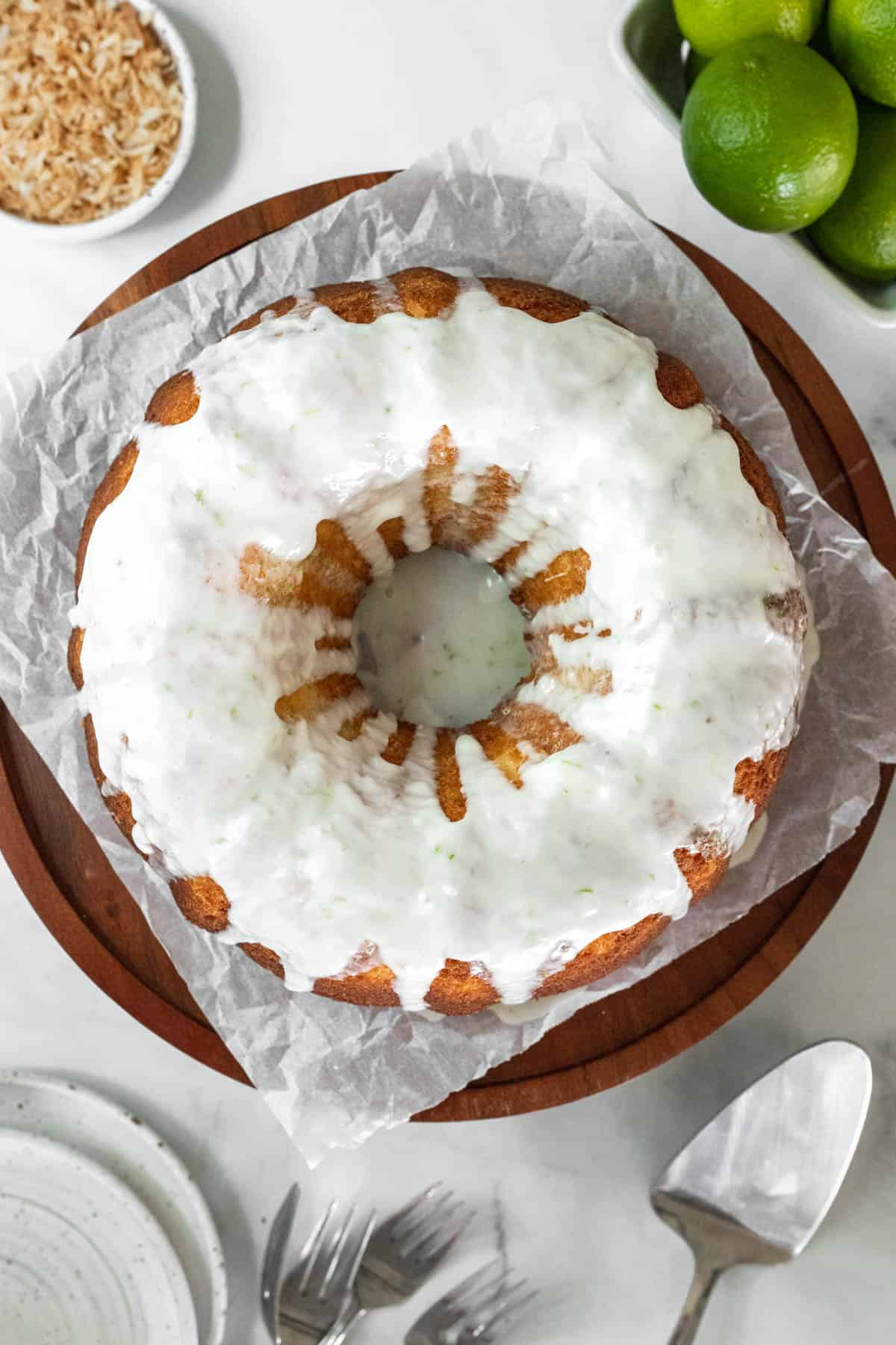 Coconut lime cake on a cake stand and drizzled with glaze.