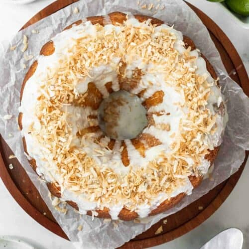 Coconut lime drizzle cake on a wooden cake stand with fresh limes around it.