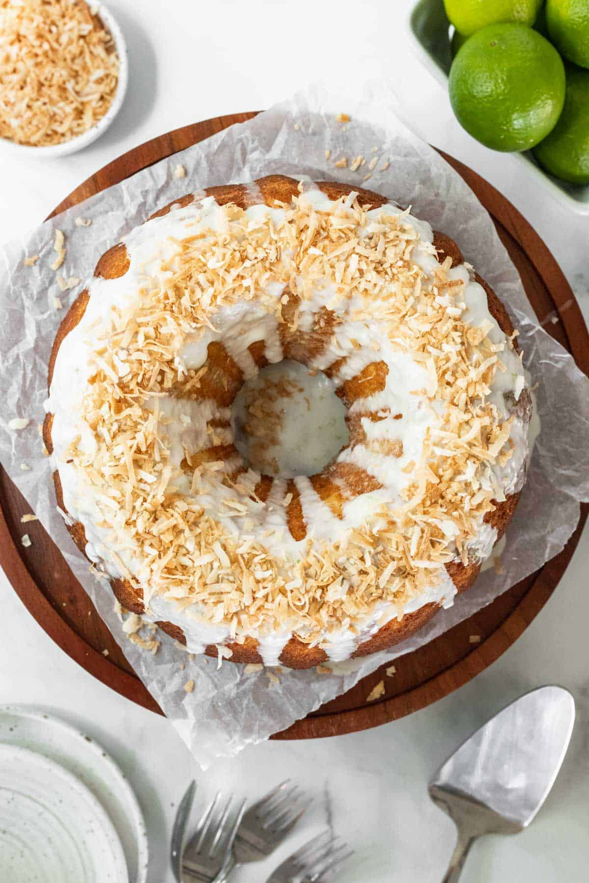 Coconut lime drizzle cake garnished with toasted coconut on a wooden cake stand with fresh limes around it.