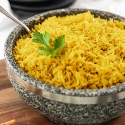 Easy homemade yellow rice in a stone bowl with a serving spoon.