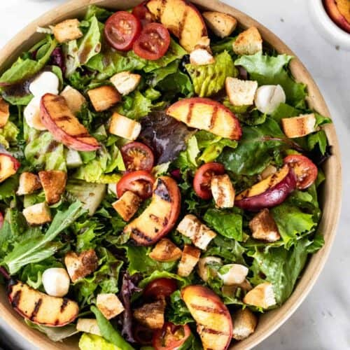 Bruschetta salad in a large bowl topped with grilled peaches, mozzarella, croutons, and sliced tomatoes.