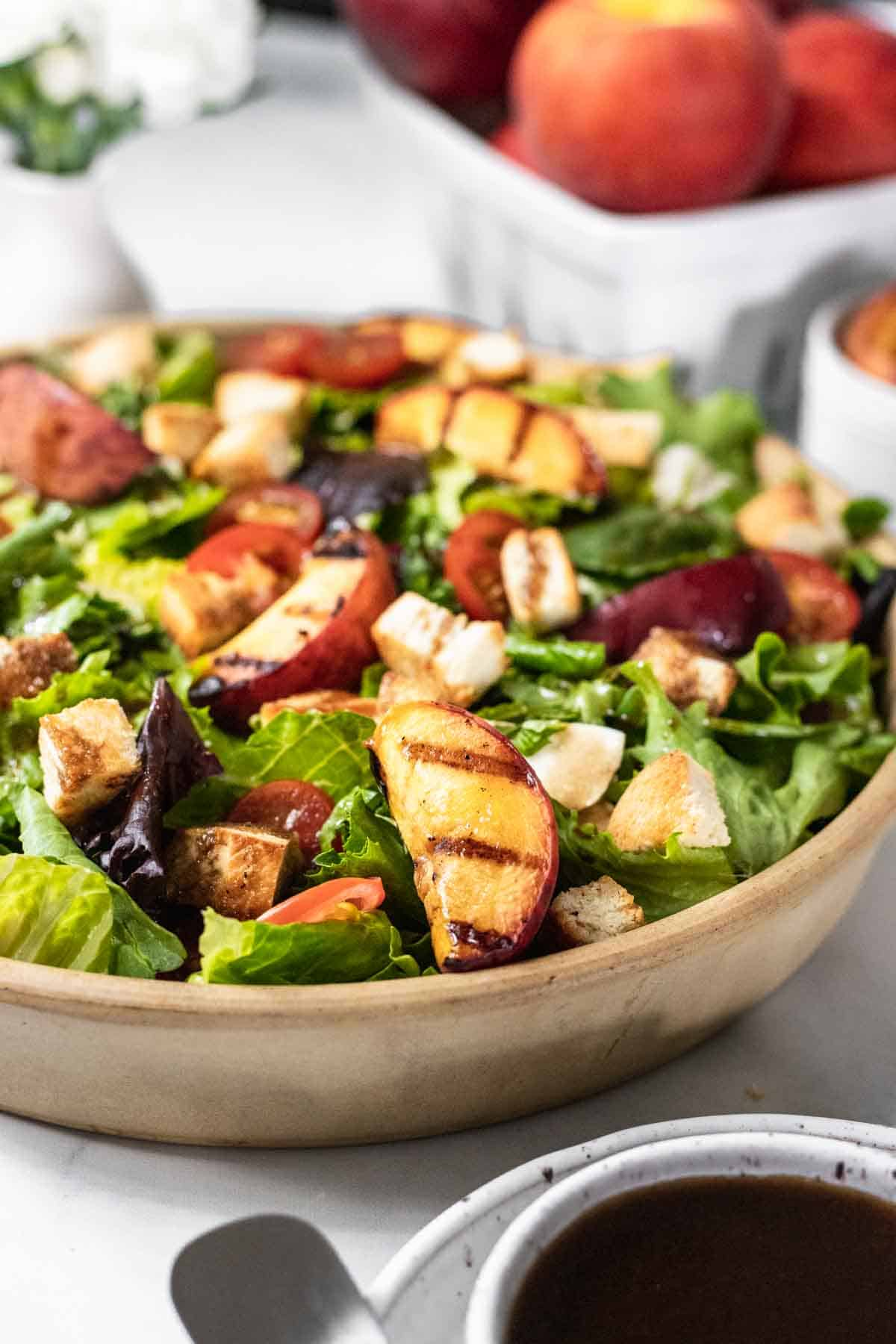 Bruschetta salad in a bowl with grilled peaches and whole fresh peaches in a basket behind it.