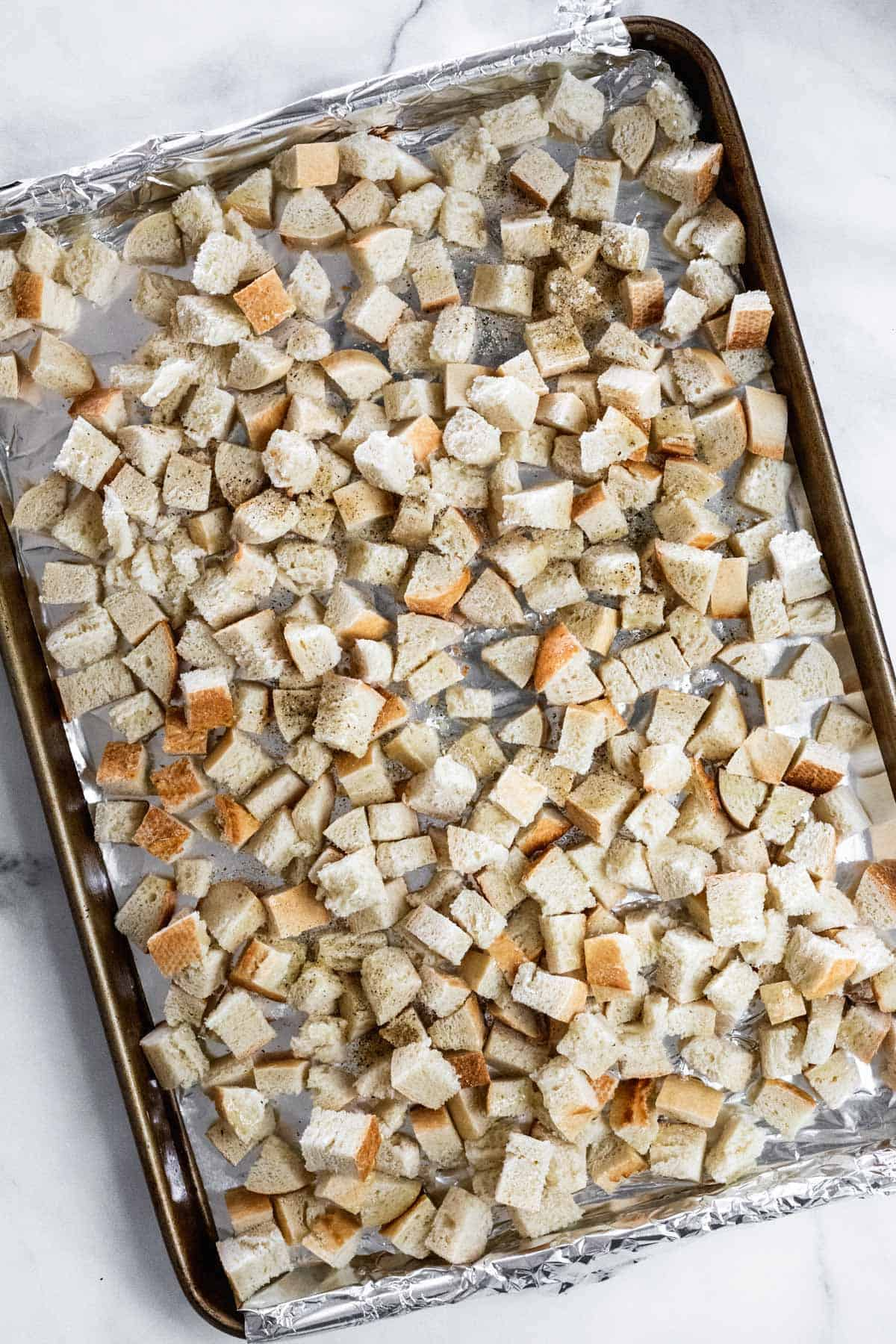 Diced and seasoned baguette on a sheet pan.