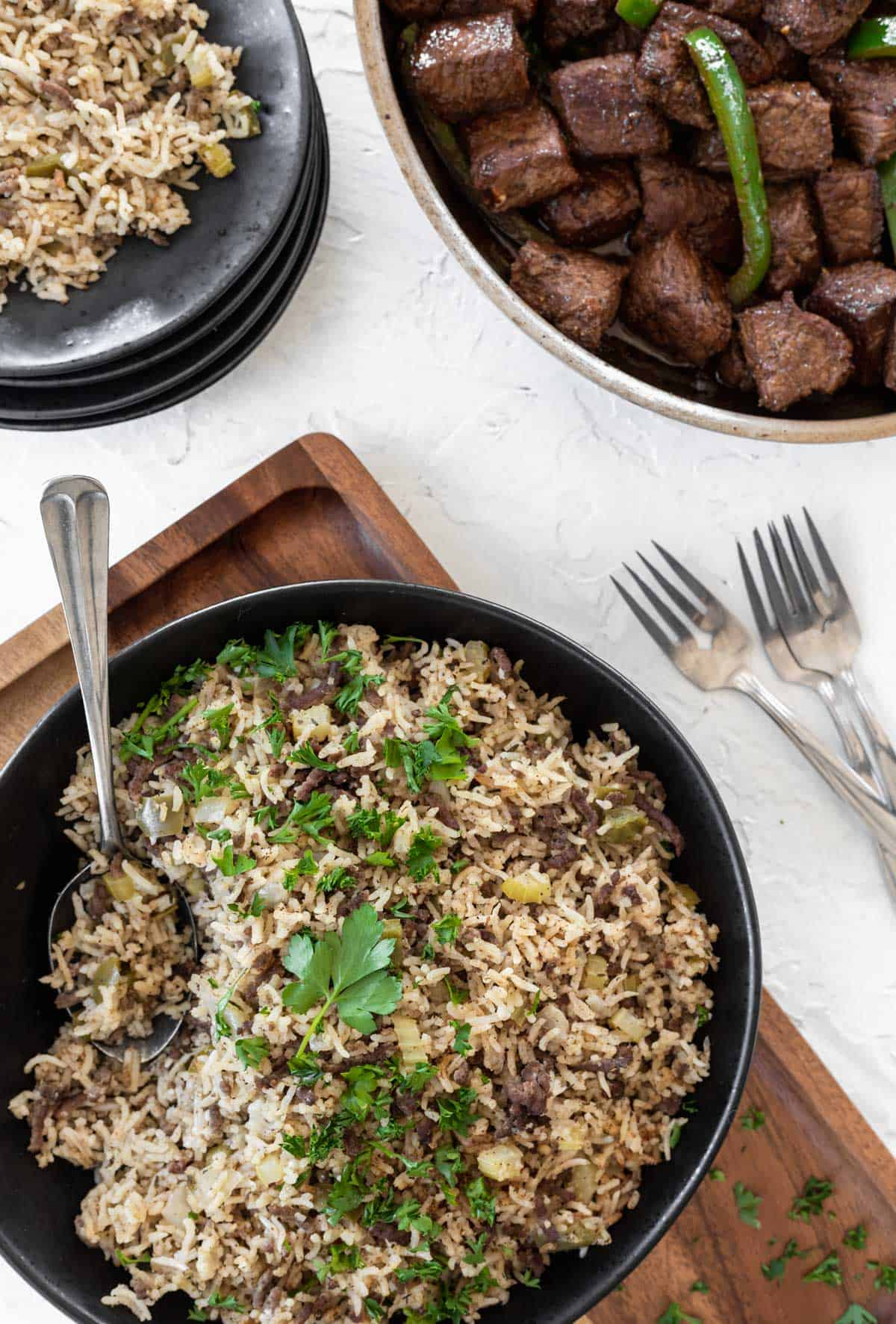 Instant pot dirty rice in a bowl with a serving spoon, a black plate with some rice on it, and a skillet of cajun steak bites off to the side.