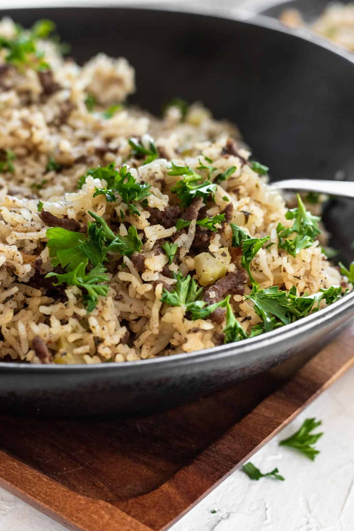 Dirty rice garnished with parsley in a black bowl.
