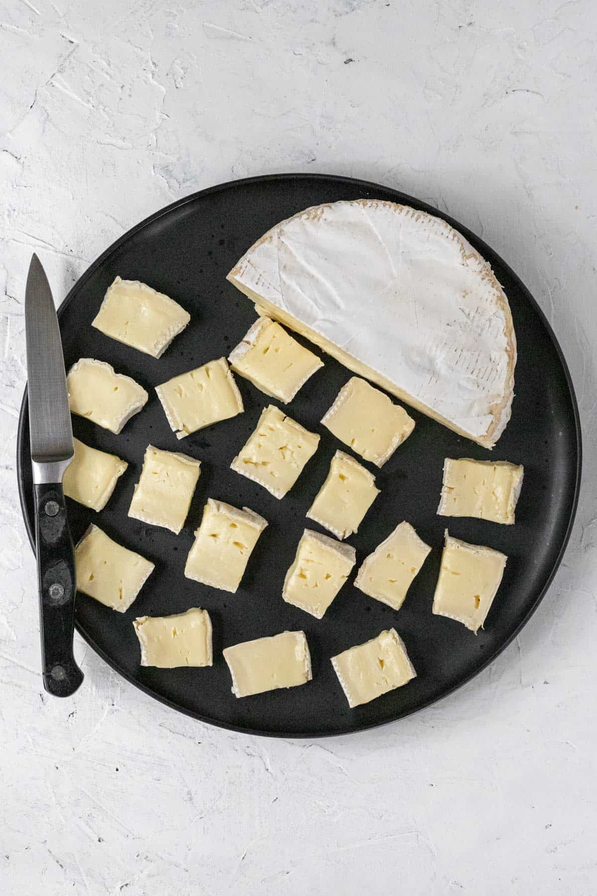 Cubed brie on a plate with a knife.