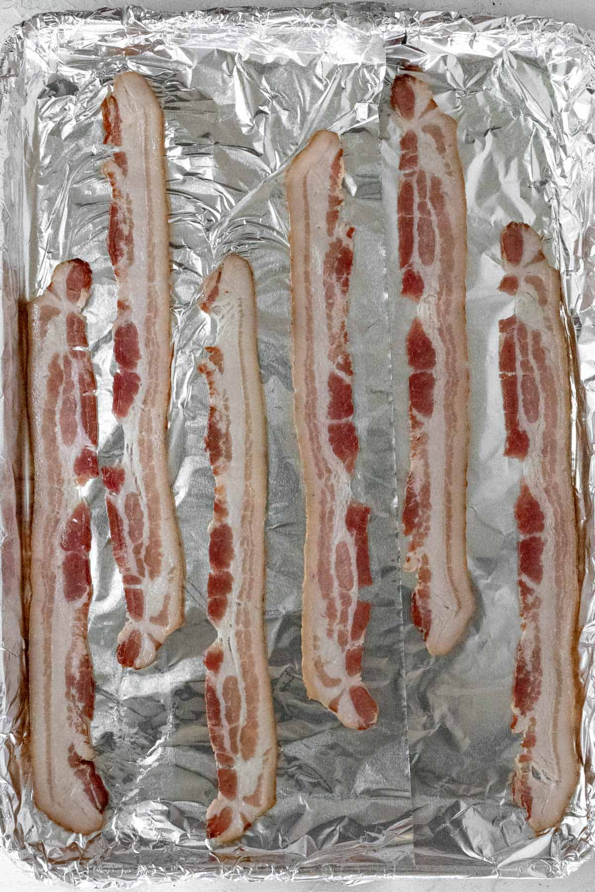 Strips of bacon on a sheet pan before going in the oven.