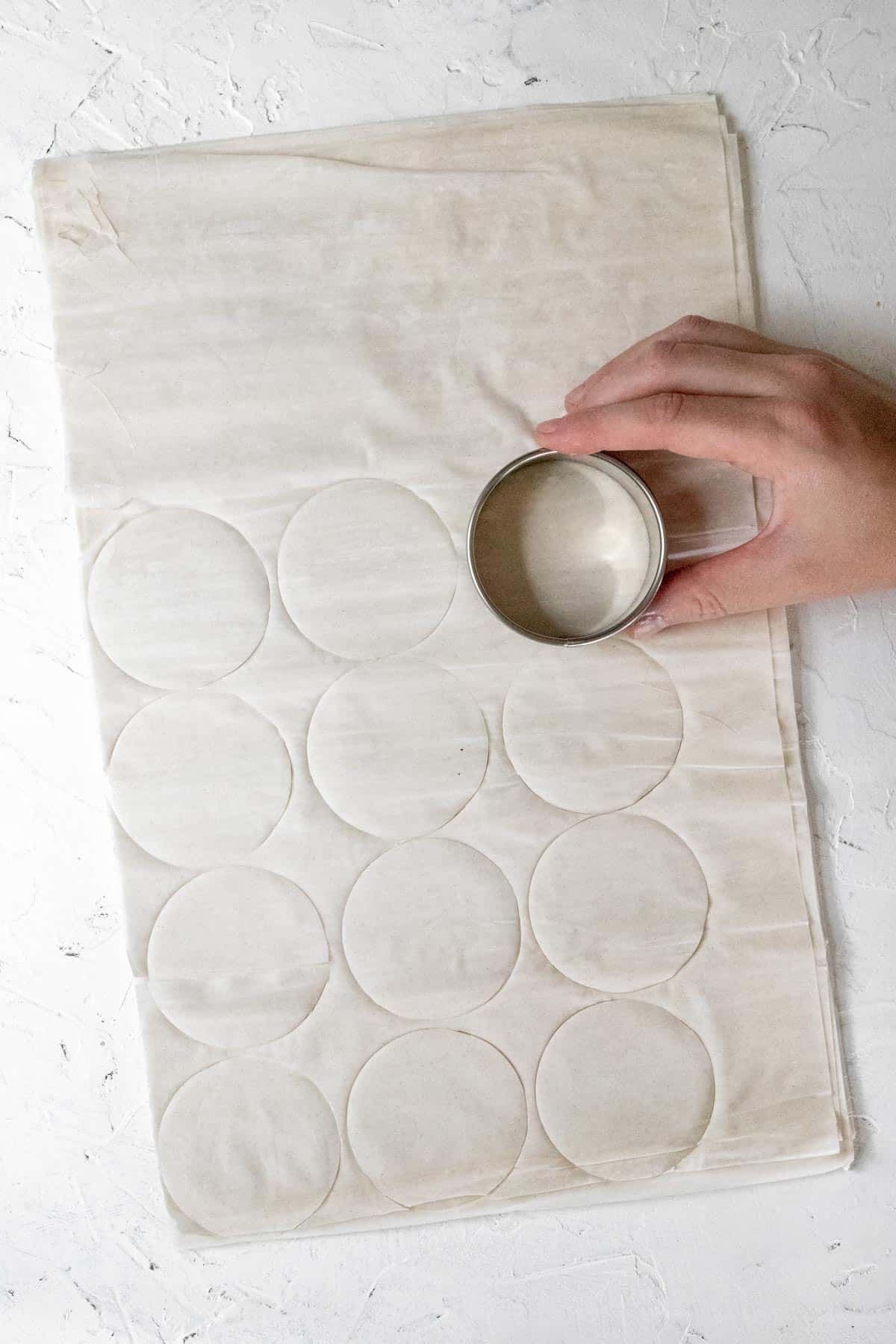 A hand with a circular cookie cutter cutting circles of phyllo dough.