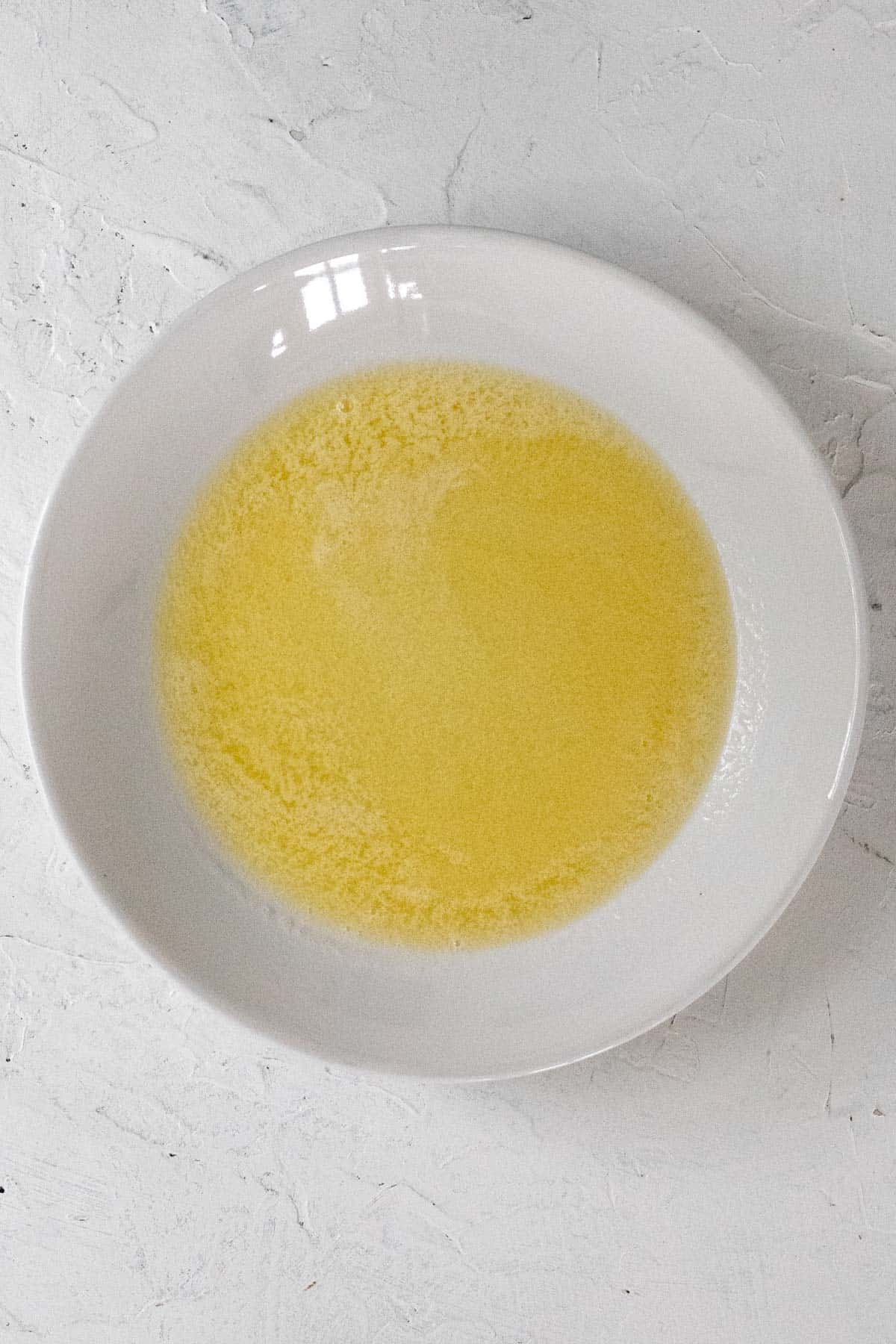 Melted butter in a white bowl.