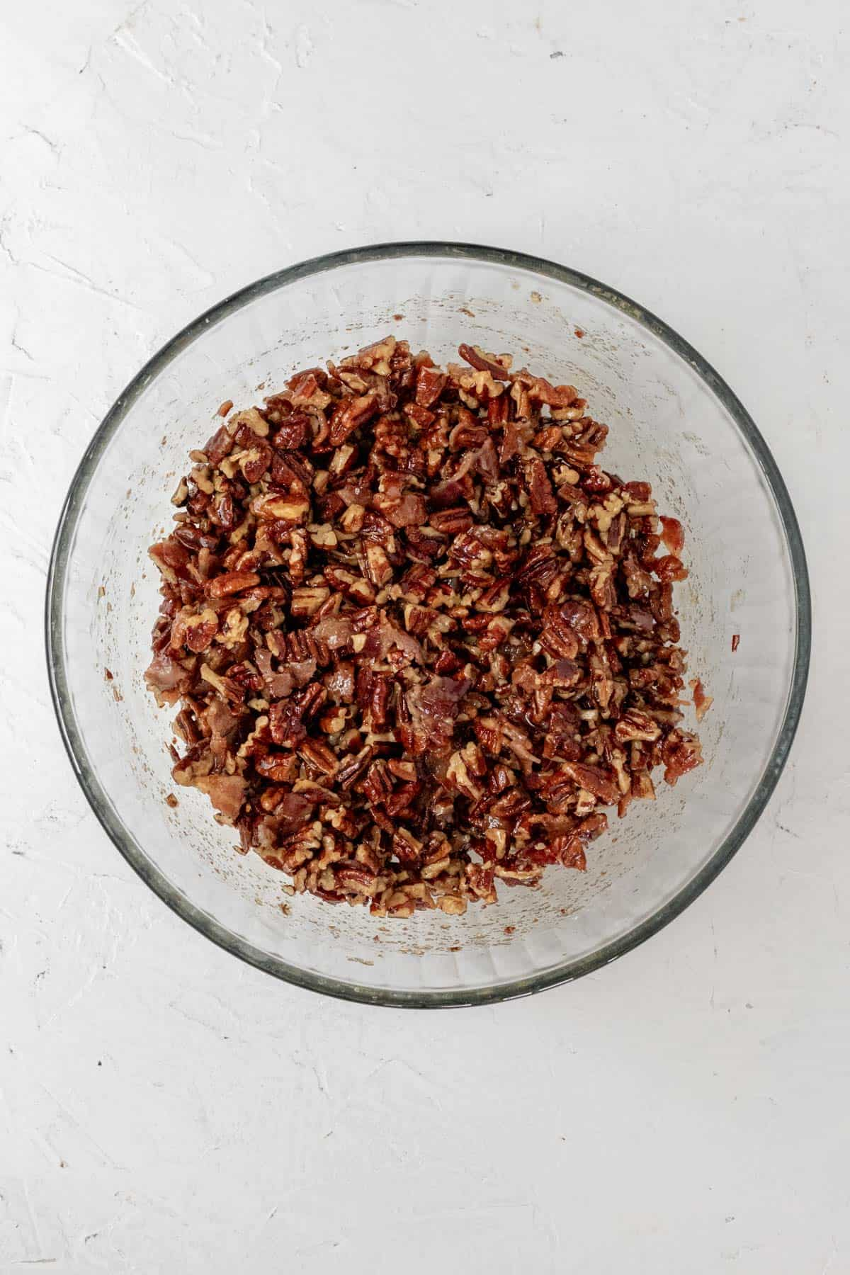 A mixture of bourbon, bacon, pecans, brown sugar, and melted better in a large glass mixing bowl.