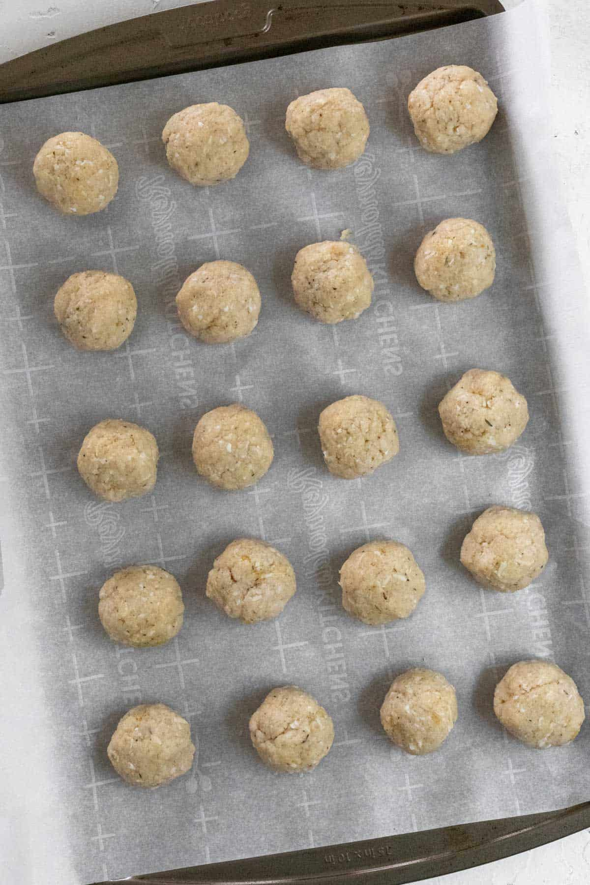 Raw meatball mixture formed into meatballs and lined up on a sheet pan.