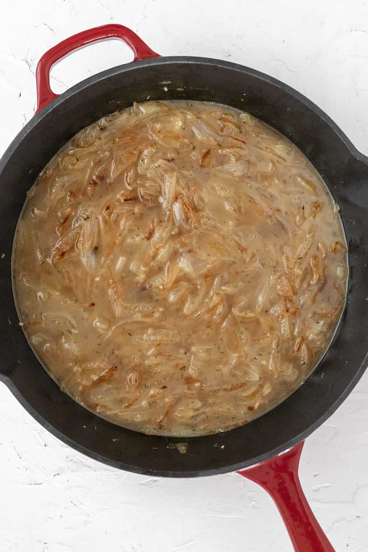 Broth added to the cast iron skillet with the caramelized onions.