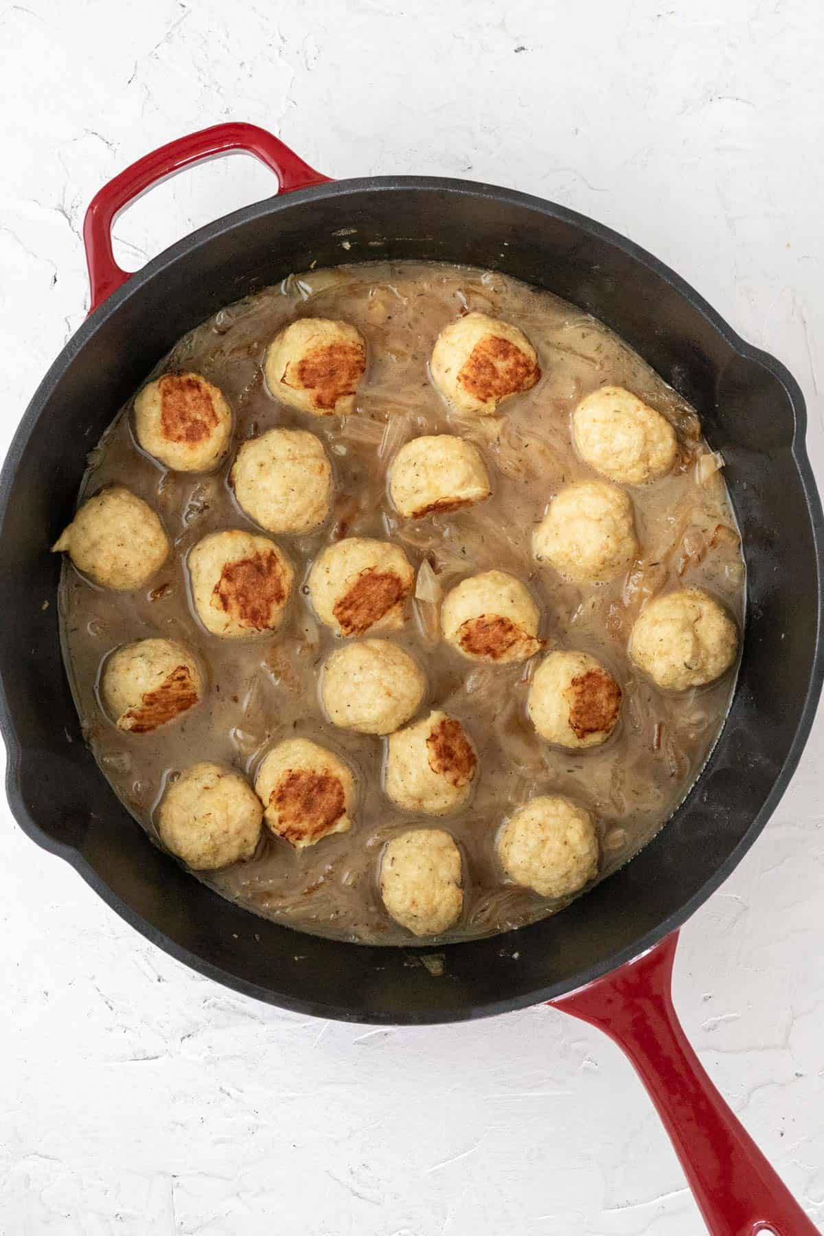 Baked chicken meatballs added to the skillet with the caramelized onions and chicken broth.