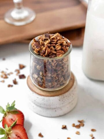 Homemade apple cinnamon granola in a glass jar with a jar of milk and fresh strawberries around it.