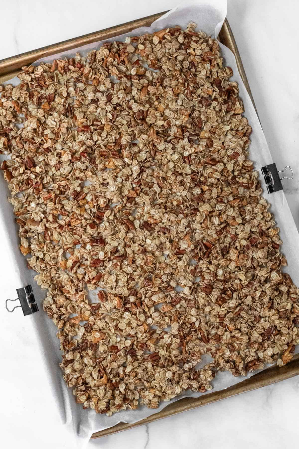 Granola ingredients spread out on a baking sheet before going in the oven.